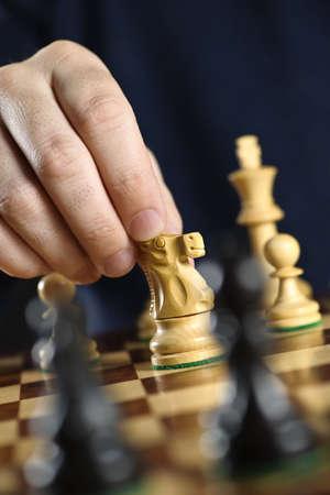 Schachmatt: Hand, die ein Ritter-Schachfigur auf Holz Schachbrett verschieben