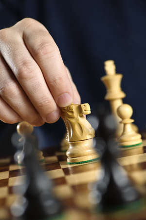 competitor: Hand moving a knight chess piece on wooden chessboard Stock Photo