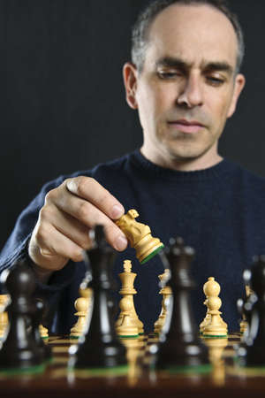 Man moving a chess piece on wooden chessboard photo
