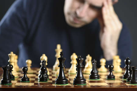 Chessboard with man thinking about chess strategy Imagens - 25381831