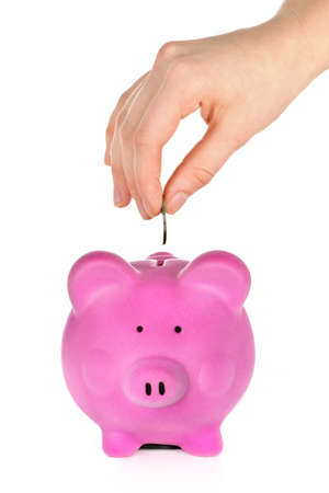 Hand putting coin into pink piggy bank slot photo