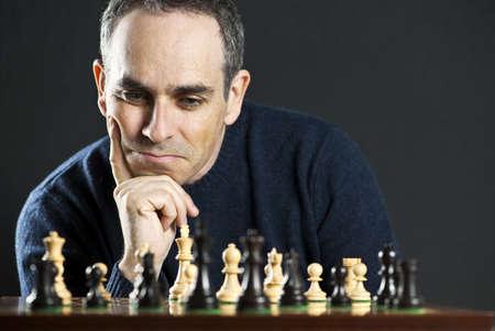 jugando ajedrez: Tablero de ajedrez con hombre pensando en estrategia de ajedrez Foto de archivo