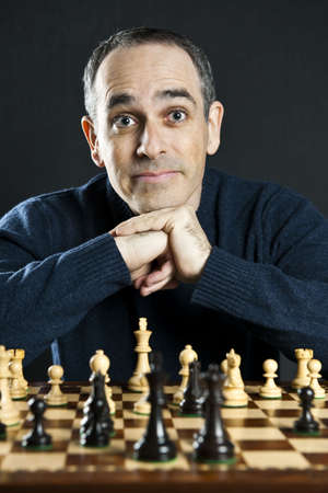 Chessboard with man thinking about chess strategy Imagens