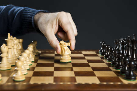Hand moving a knight chess piece on wooden chessboard photo