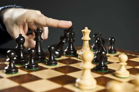 chess board: Finger pushing over King chess piece in defeat Stock Photo