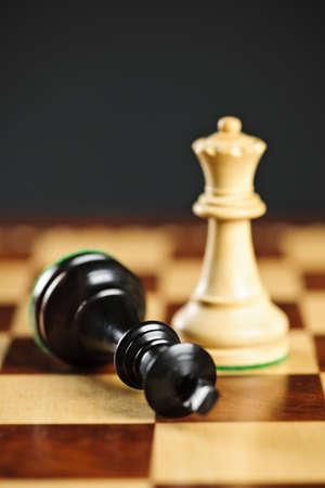tablero de ajedrez: Detalle de jaque mate en rey por ganar en el juego de ajedrez de la reina