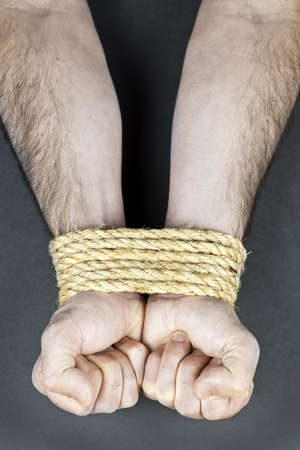 Male hands tied up with strong rope photo