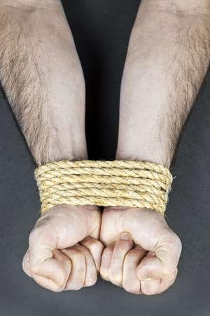 atados: Manos masculinas atado con una cuerda fuerte