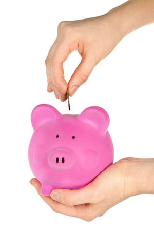 pennypinching: Hand putting coin into pink piggy bank slot