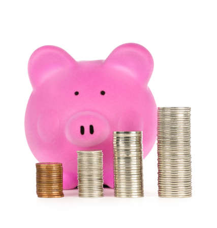 Stacks of coins in front of pink piggy bank showing growth photo