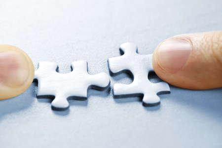 matching: Dedos empujando la coincidencia de dos piezas del rompecabezas juntos