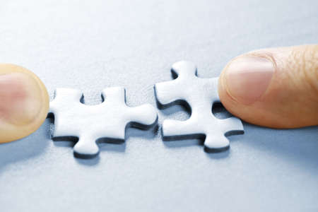 Fingers pushing two matching puzzle pieces together photo