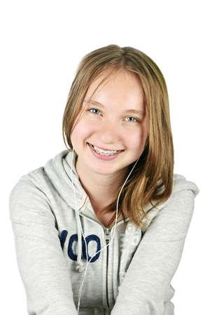 Isolated portrait of beautiful teenage girl listening to earphones