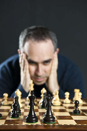 Chessboard with man thinking about chess strategy Stok Fotoğraf