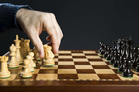 Hand moving a knight chess piece on wooden chessboard Imagens