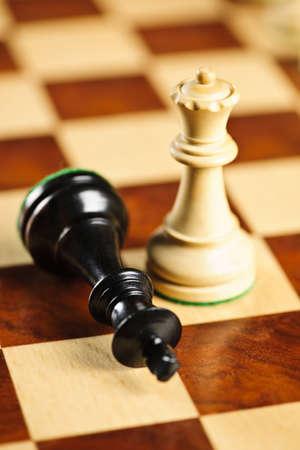 jugando ajedrez: Detalle de jaque mate en rey por ganar en el juego de ajedrez de la reina Foto de archivo