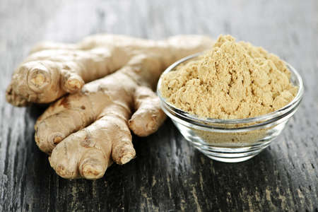 spice: Fresh and ground ginger root spice on wooden table