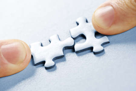 Fingers pushing two matching puzzle pieces together Stock Photo - 6856913