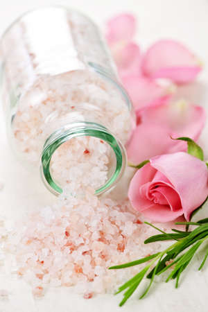 bath: Pink bath salts in a glass jar with flowers and herbs Stock Photo