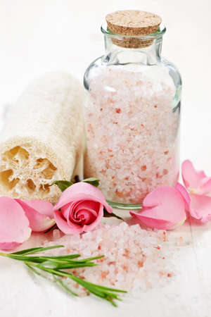 Pink bath salts in a glass jar with flowers and herbs photo