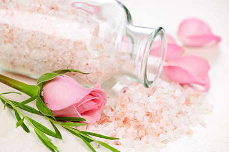 Pink bath salts in a glass jar with flowers and herbs Banco de Imagens