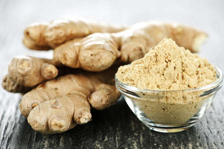 Fresh and ground ginger root spice on wooden table photo
