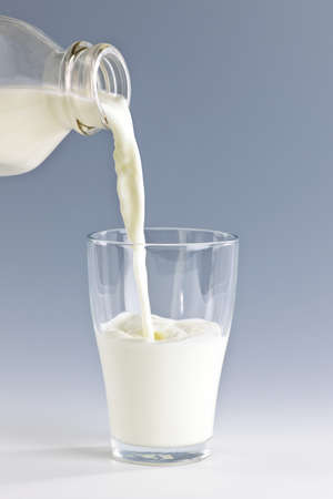 glass of milk: Pouring fresh white milk from bottle into a glass Stock Photo