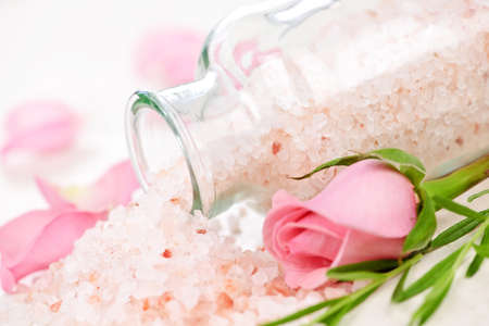 salts: Pink bath salts in a glass jar with flowers and herbs Stock Photo