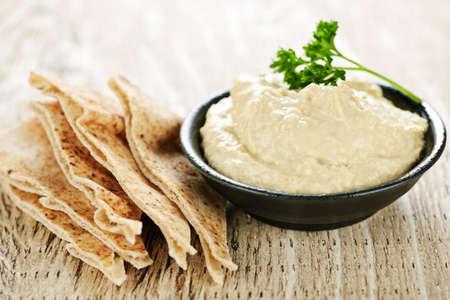 Bowl of fresh hummus dip with pita bread slices