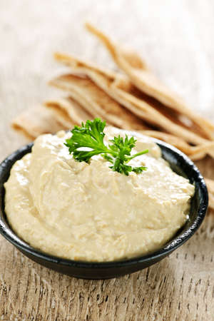 Bowl of fresh hummus dip with pita bread slices photo