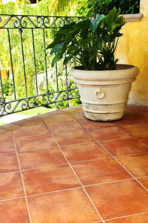 tile flooring: Tiled Mexican balcony with potted plant near railing Stock Photo