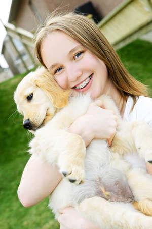 Portrait of smiling teenage girl holding golden retriever puppy photo