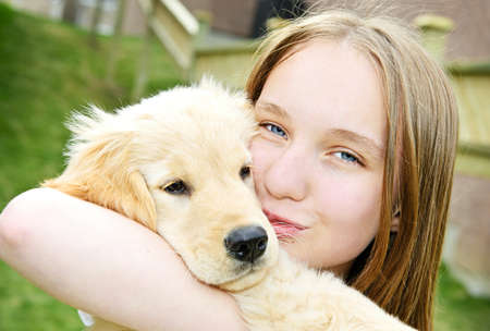 Portrait of smiling teenage girl holding golden retriever puppy Stock fotó