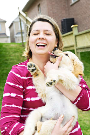 Portrait of laughing woman holding golden retriever puppy photo