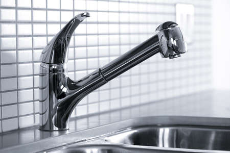 sleek: Stainless steel kitchen faucet and sink with tile backsplash