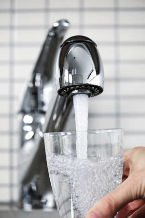 Filling glass of water from stainless steel kitchen faucet