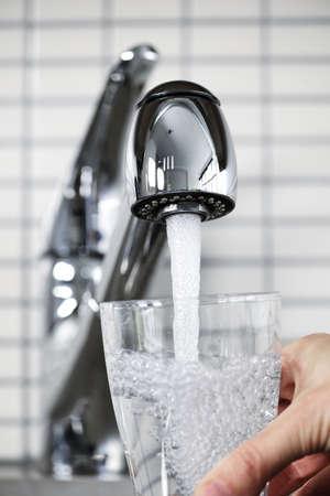 rubinetti: Riempimento bicchiere d'acqua dal rubinetto da cucina in acciaio inox Archivio Fotografico