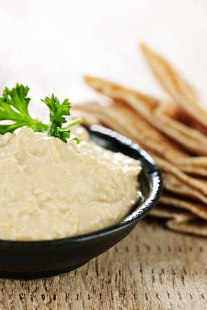 pita: Bowl of fresh hummus dip with pita bread slices