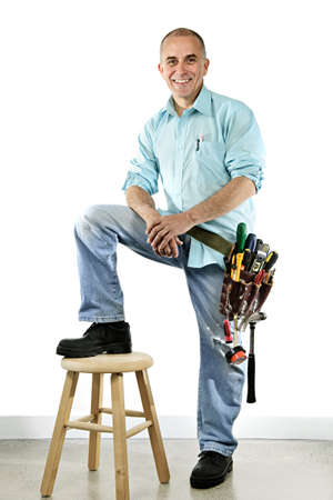 stool: Portrait of smiling handyman with tool belt and stool Stock Photo