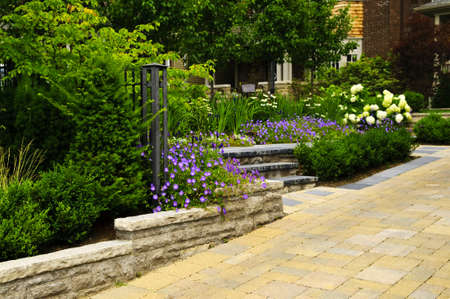pavers: Natural stone landscaping in front of a house with lush green garden Stock Photo