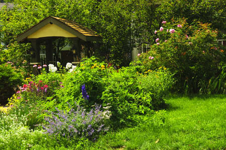 Lush green landscaped garden with flowers and gazebo photo