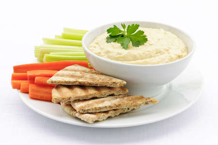 dipping: Healthy snack of hummus dip with pita bread slices and vegetables