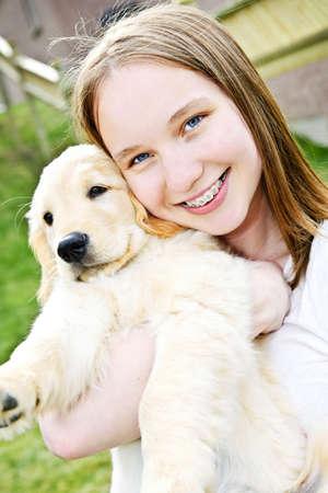 cute teen girl: Portrait of smiling teenage girl holding golden retriever puppy Фото со стока