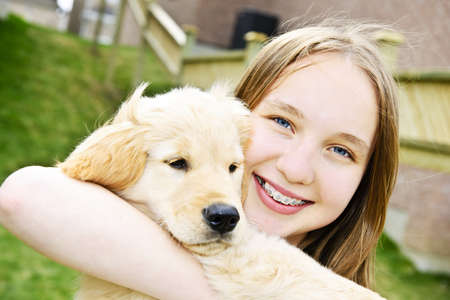amigos abrazandose: Retrato de sonriente chica adolescente celebración golden retriever puppy