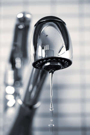 Water dripping from stainless steel kitchen faucet photo