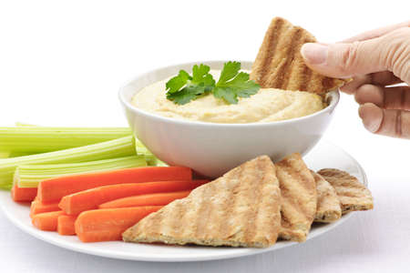 dipping: Hand dipping slice of pita bread into bowl of hummus