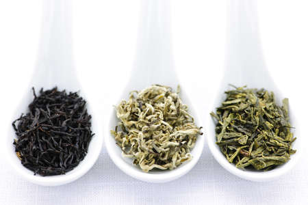 Black, white and green dry tea leaves in spoons Archivio Fotografico