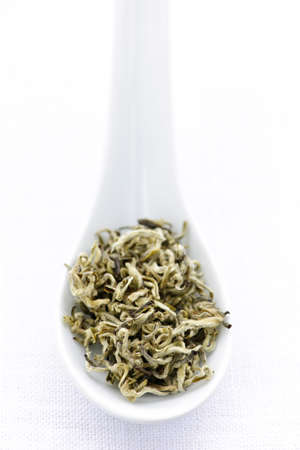 White dry tea leaves on a spoon