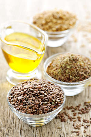 linseed oil: Bowls of whole and ground flax seed with linseed oil Stock Photo