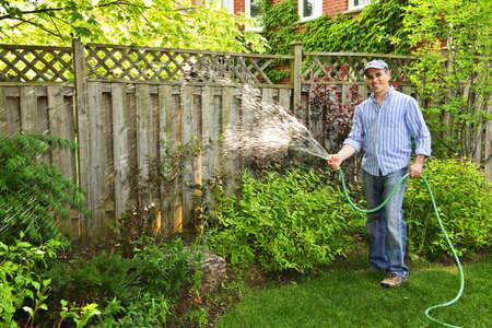 Mann, die Bewässerung des Gartens mit Schlauch im Hinterhof